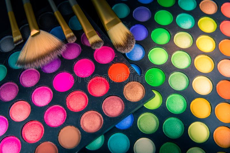 Palette of multicolor cosmetic make up: eye shadows with brushes stock images