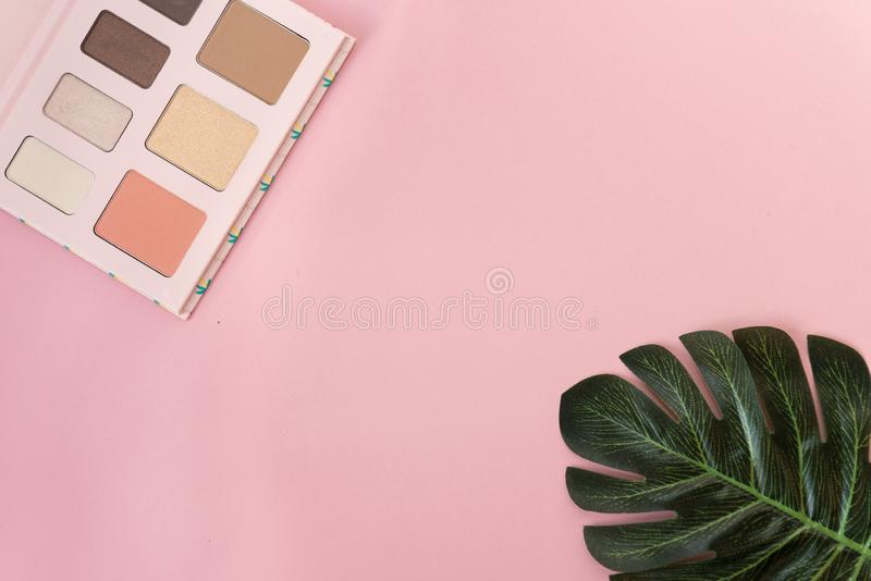 Palette of multicolor cosmetic make up with a monstera leaf on pink background. Pastel color palette, minimalism, light pink stock photography