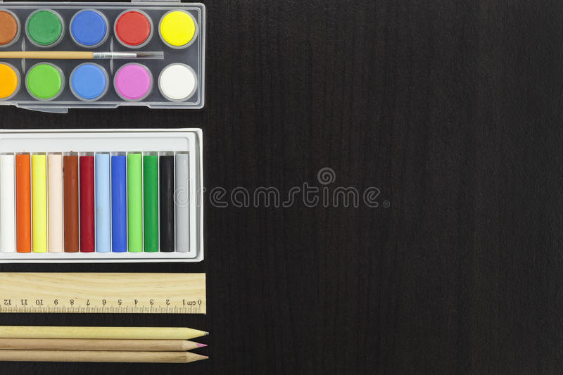 palette with paint and brush,pencil,ruler,colorful chalk on dark royalty free stock photography