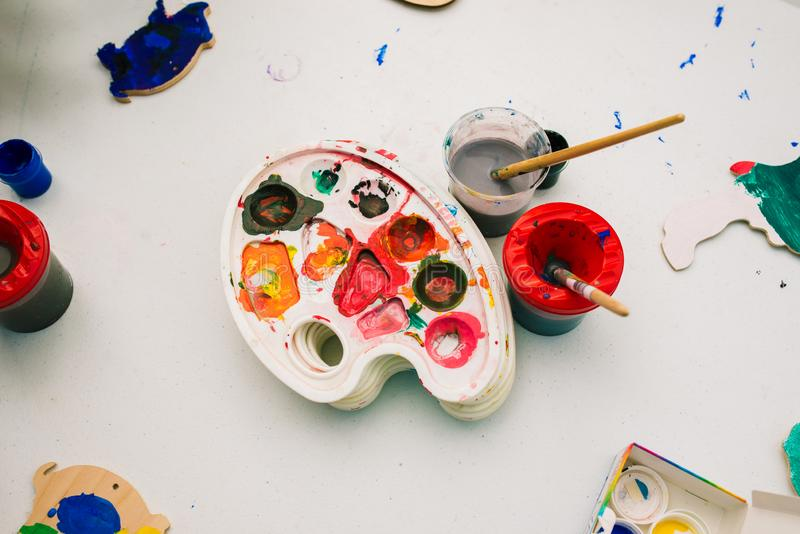 Palette and paint brushes. Cans with paints and water on the table. Watercolor painting. The concept of drawing, creativity and royalty free stock image