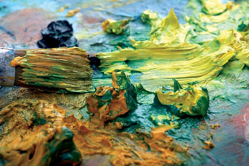 Palette with paint and brushes. Structure full of colors stock images