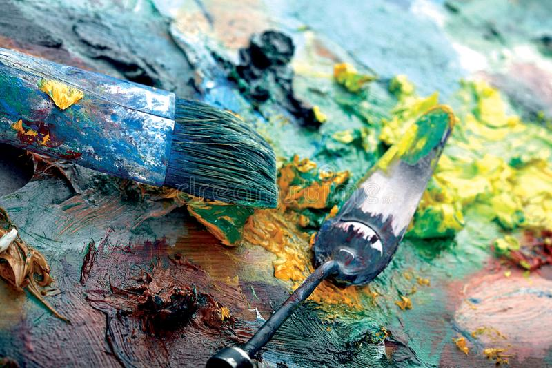 Palette with paint and brushes. Structure full of colors stock photography