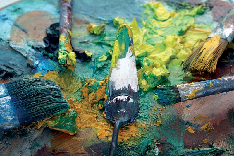 Palette with paint and brushes. Structure full of colors royalty free stock photography