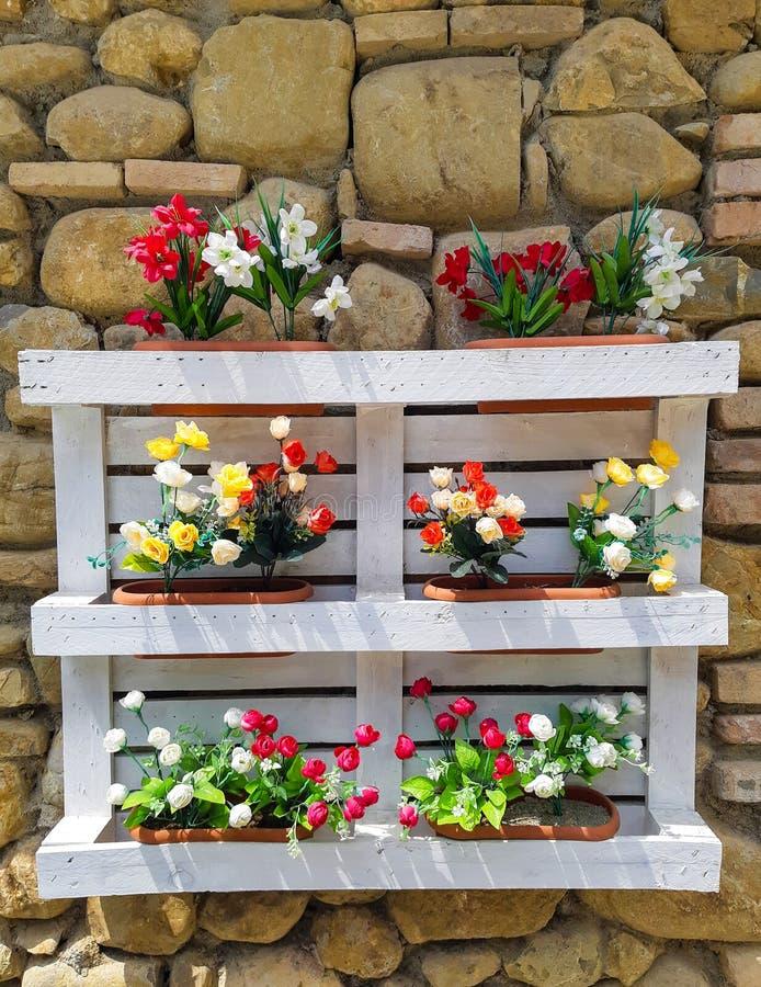 Palette reconstruite dans des boîtes de fleur avec le mur rustique image libre de droits