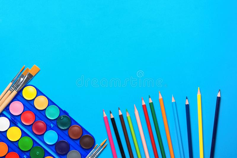 Palette with Rows of Multicolored Watercolor Paints Brushes Pencils on Blue Background. Arts School Class Creativity Painting royalty free stock images