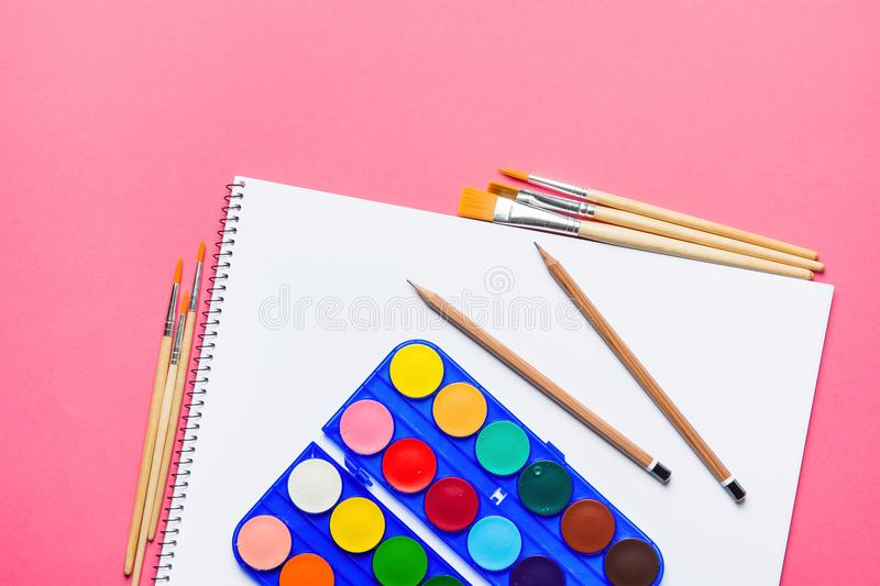 Palette with Rows of Multicolored Watercolor Paints Brushes Pencils Sketchbook on Pink Background. Arts School Class Creativity royalty free stock image