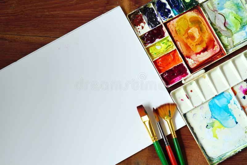 Palette of watercolor with brush various size and white paper on wooden texture background. royalty free stock images