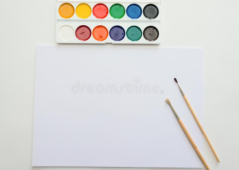 Palette of watercolor paints, brushes and paper for a water color on white background royalty free stock images