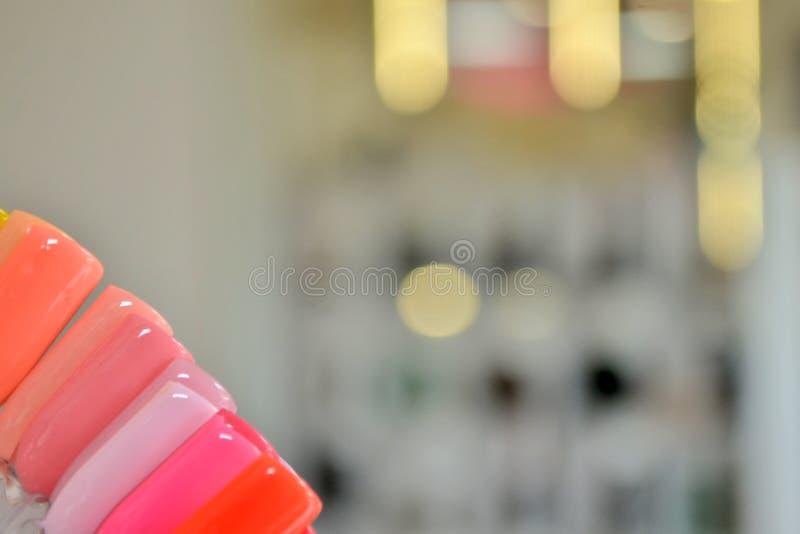 Paletten med rosa färgprövkopior av stelnar polermedel i hörn, mot en bakgrund av oskarpa ljusa kulor och speglar royaltyfria bilder