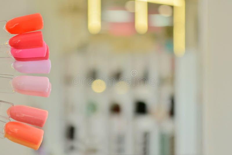 Paletten med rosa färgprövkopior av stelnar polermedel, mot en bakgrund av oskarpa ljusa kulor och speglar arkivfoto