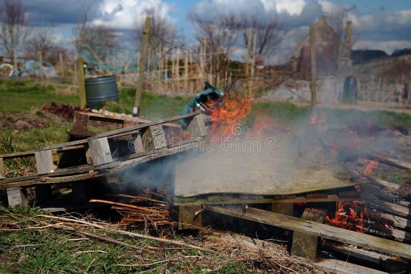 Palettes en bois et déchets généraux étant brûlés image stock