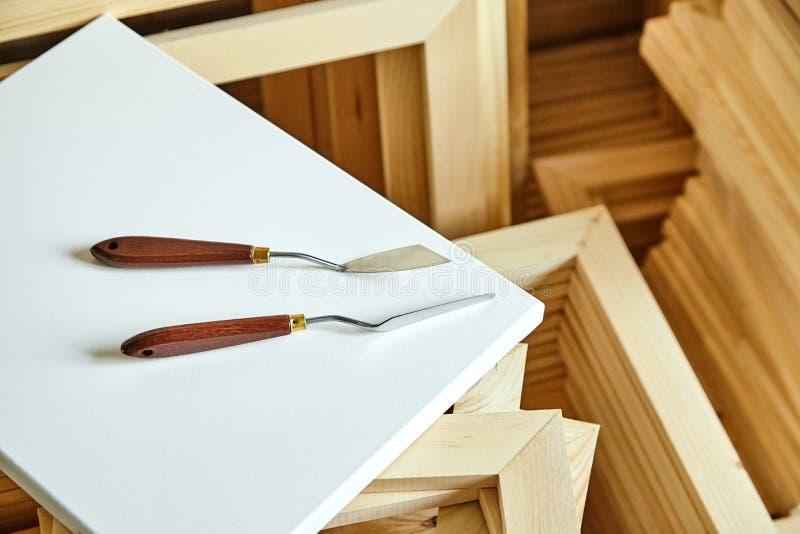 Palettknivar som ligger på en vit bomullskanfas träbårar arkivfoto