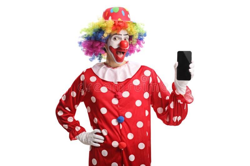 Palhaço alegre que guarda um telefone celular e que olha a câmera fotos de stock