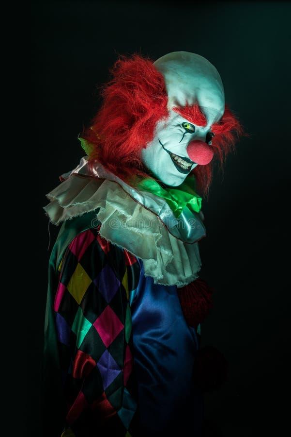 Palhaço assustador em um fundo escuro imagem de stock