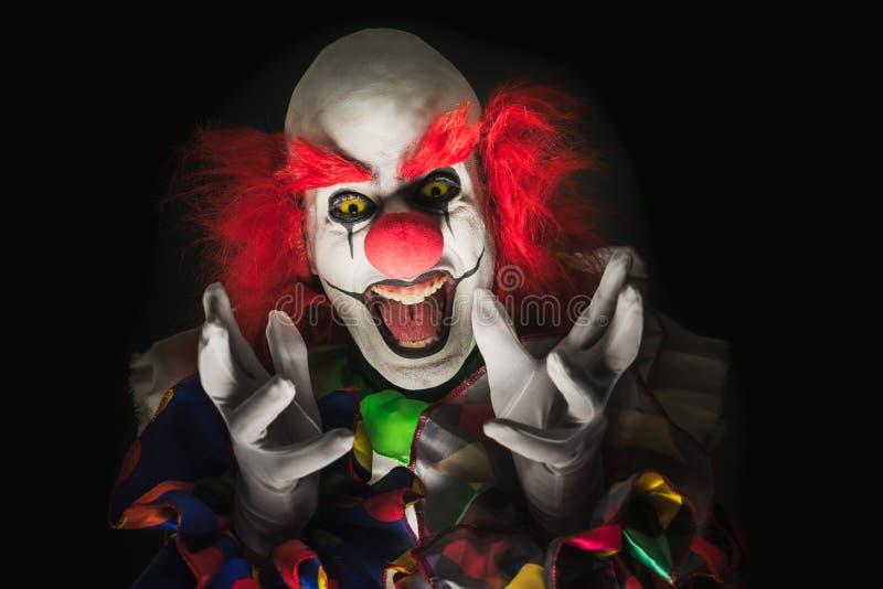 Palhaço assustador em um fundo escuro fotos de stock