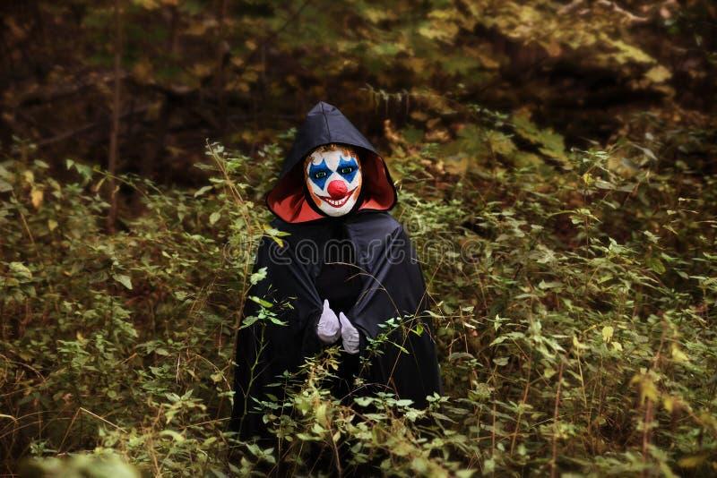 Palhaço assustador na floresta na capa fotos de stock royalty free