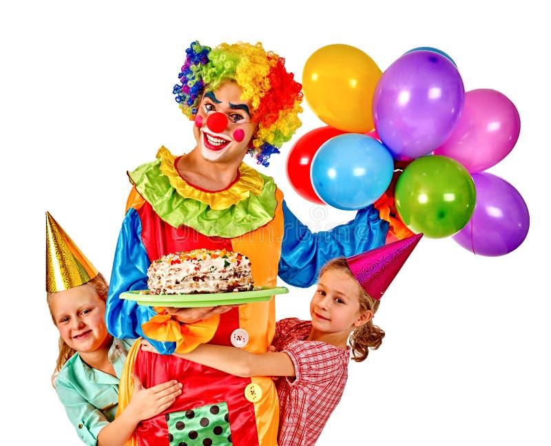 Palhaço com o bolo da terra arrendada do baloon no grupo do aniversário fotos de stock