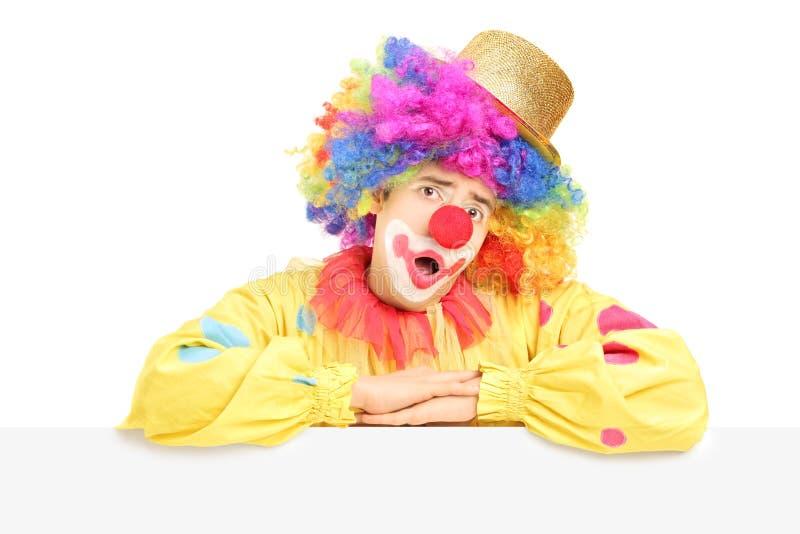 Palhaço de circo masculino que faz uma careta em um painel vazio imagens de stock royalty free