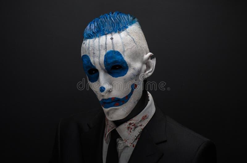 Palhaço terrível e tema de Dia das Bruxas: Palhaço azul louco no terno preto isolado em um fundo escuro no estúdio imagens de stock royalty free