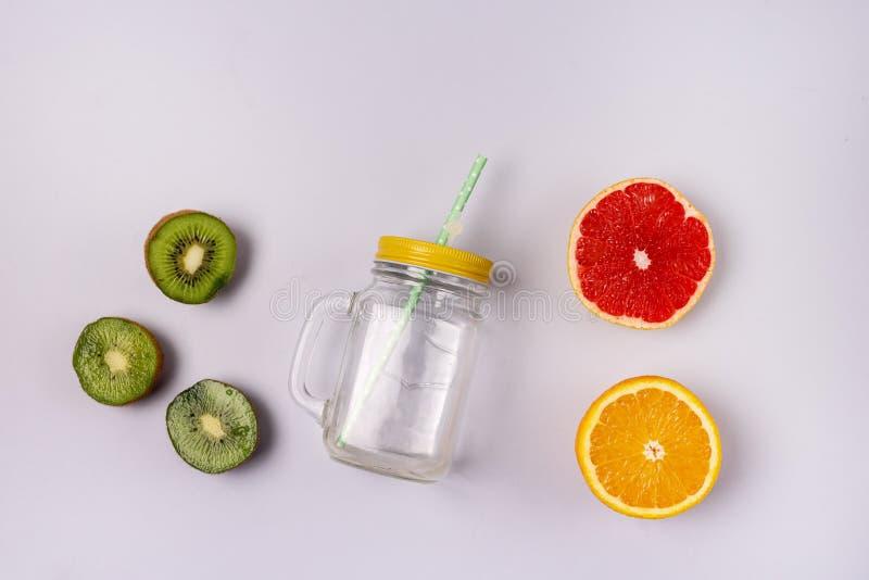 Palha de caneca de vidro jar no fundo azul Detox ou Conceito de dieta Kiwi Orange Grapefruits Ingredient for Smoothie or Juice To fotografia de stock royalty free
