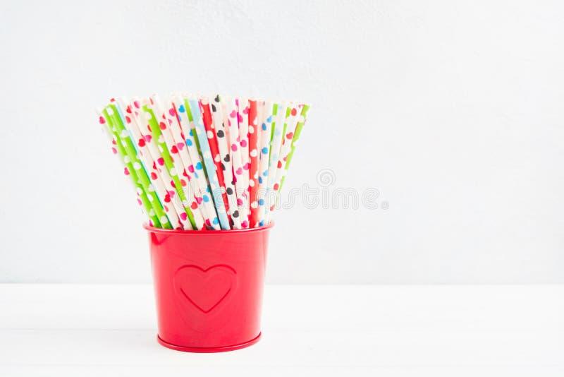 Palha de papel com corações para o dia de Valentim na cubeta vermelha com coração fotos de stock royalty free