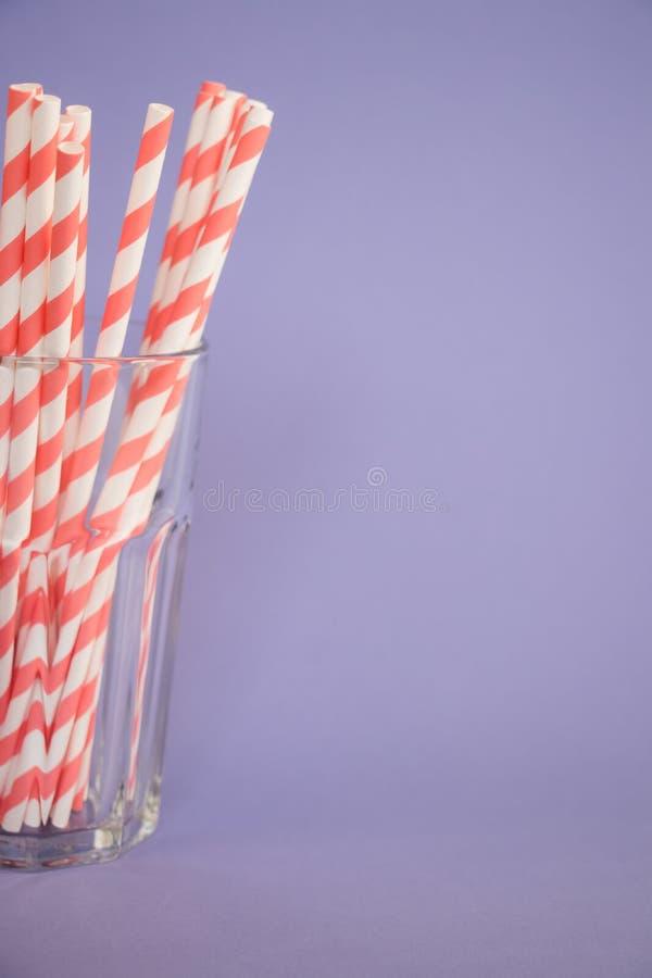 Palha para cocktail com linhas corais e brancas no vidro em um fundo violeta pastel imagens de stock royalty free