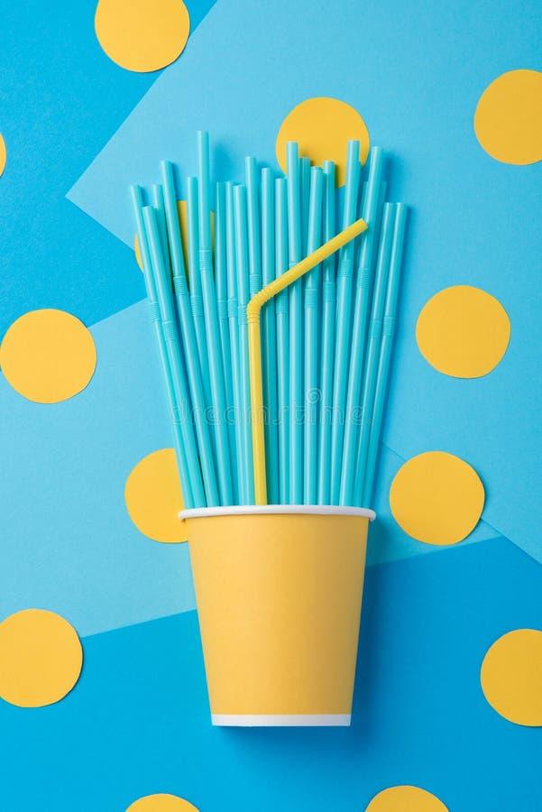 Palhas amarelas e azuis para um partido nos copos de papel em um CCB brilhante foto de stock