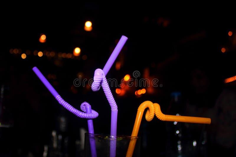 Palhas em uma bebida em um restaurante na noite imagem de stock