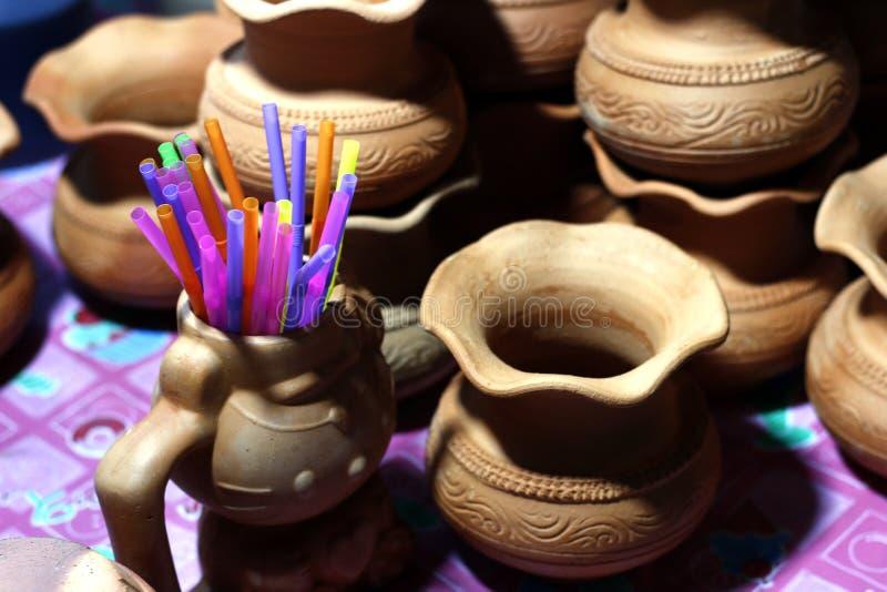 Palhas plásticas no potenciômetro da cerâmica para o suco doce no foco seletivo de Tailândia dos alimentos da rua do mercado da n imagens de stock royalty free