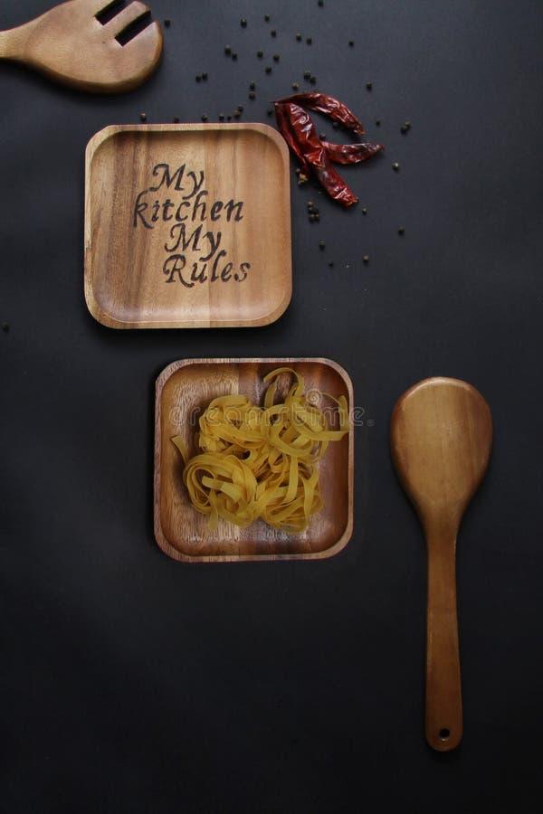 Palić na drewnianym talerzu na czarnym tło czosnku wysuszonej papryce i zdjęcie royalty free