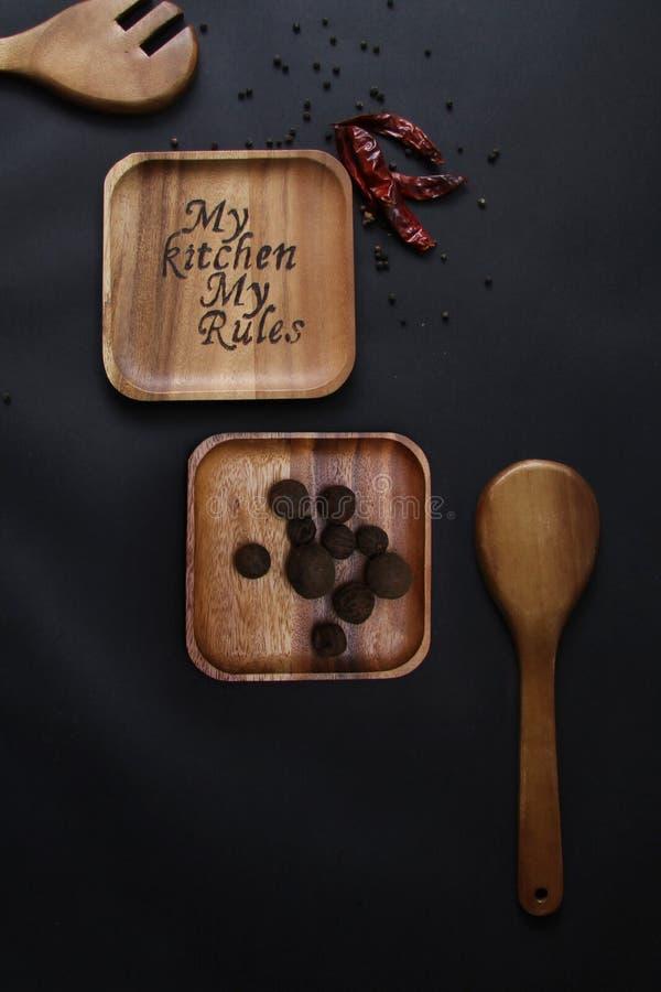 Palić na drewnianym talerzu na czarnym tło czosnku wysuszonej papryce i zdjęcia stock