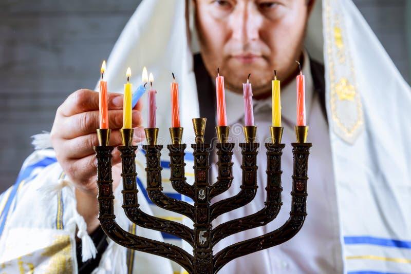 pali świeczek świętowania Hanukkah żydowskiego menorah dopatrywanie Świeczki pali w menorah mężczyzna w tle zdjęcie royalty free