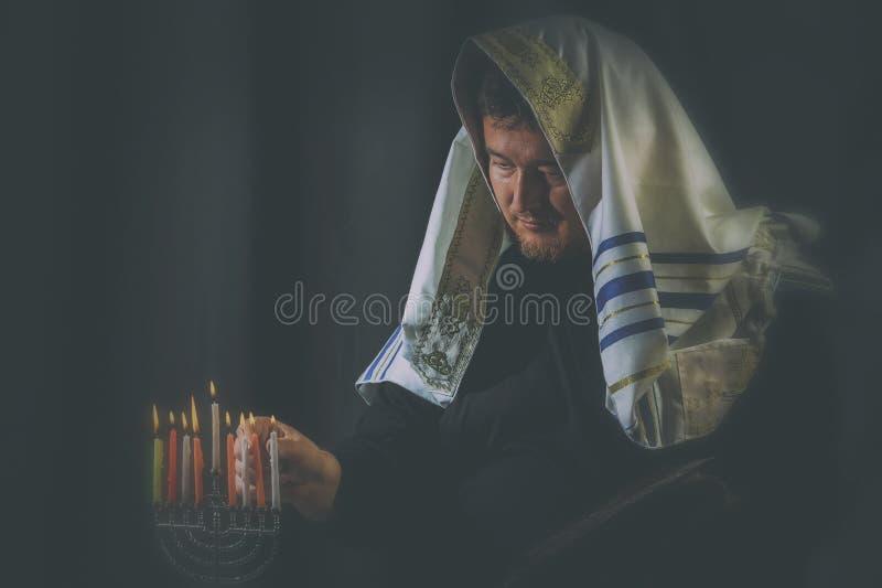pali świeczek świętowania Hanukkah żydowskiego menorah dopatrywanie Świeczki pali w menorah, mężczyzna w tle zdjęcie stock