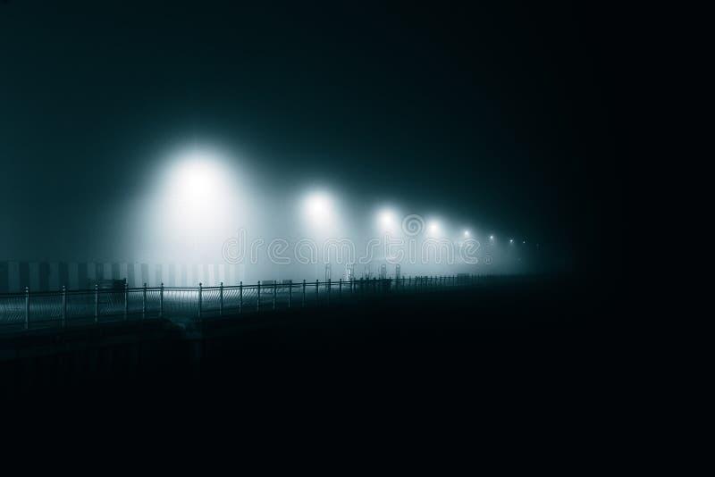 Pali della luce atmosferici nella nebbia sul lungomare/ fotografia stock