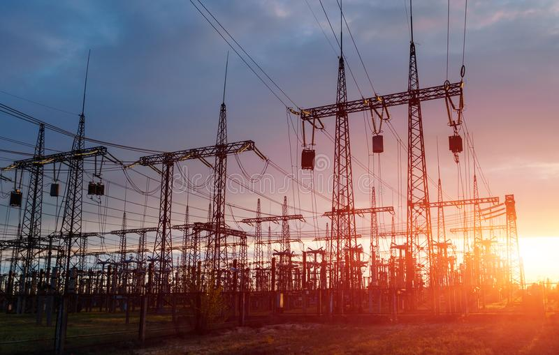 Pali di elettricità di alto potere nell'area urbana Approvvigionamento di energia, distribuzione di energia, energia di trasmissi fotografia stock libera da diritti