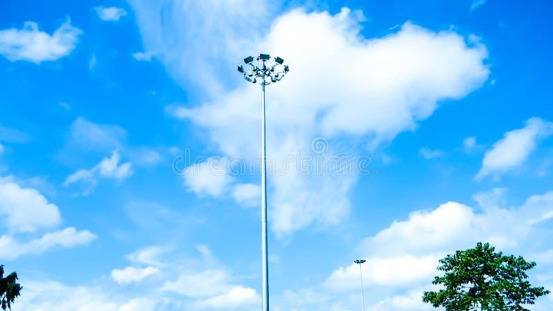 Pali di illuminazione pubblici della via contro un fondo della nuvola e del cielo blu fotografia stock libera da diritti