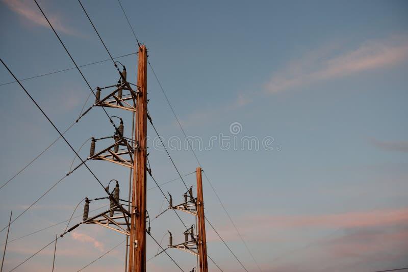 Pali pratici elettrici e linee elettriche ad alta tensione al tramonto nel Wyoming fotografie stock