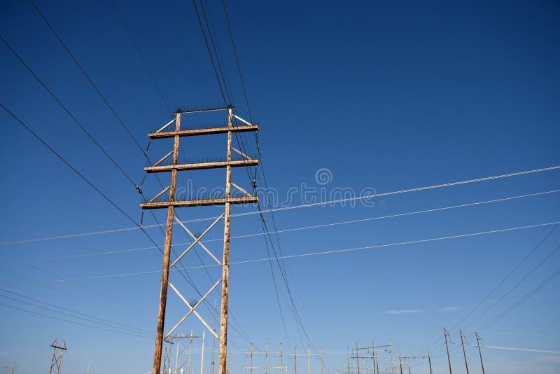 Pali pratici elettrici e linee elettriche ad alta tensione contro un cielo blu nel Wyoming fotografia stock libera da diritti