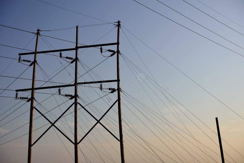 Pali pratici elettrici e linee elettriche ad alta tensione sopraelevate al tramonto fotografia stock libera da diritti