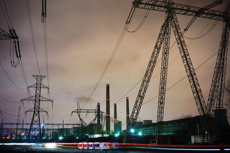 Pali tensione di alta e della centrale elettrica immagini stock