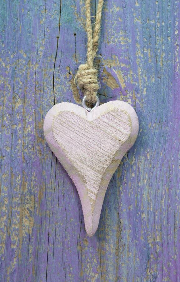 Palidezca - el corazón de madera rústico rosado en la superficie de madera púrpura para saluda imagen de archivo libre de regalías