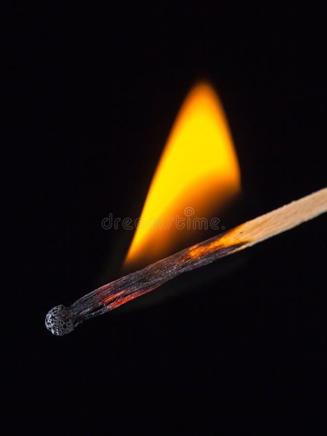 Palillo ardiendo del partido en la mano en un fondo aislado negro imágenes de archivo libres de regalías
