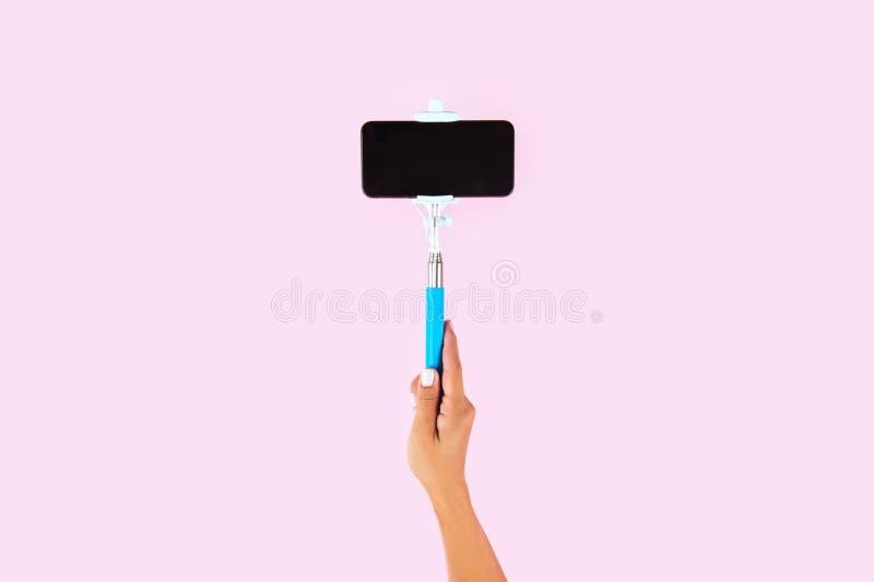 Palillo de Selfie y teléfono elegante blanco en fondo rosado fotografía de archivo