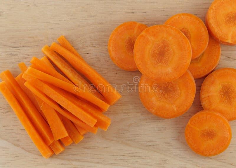 Palillo del corte de la zanahoria y redondo en la madera imagenes de archivo
