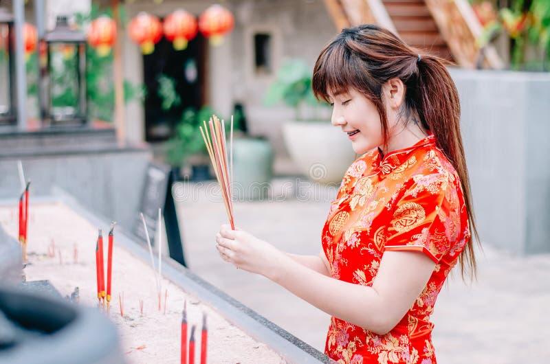 Palillos ardientes del incienso de la muchacha de la preparación del traje rojo tradicional chino lindo de Cheongsam y pagar resp foto de archivo