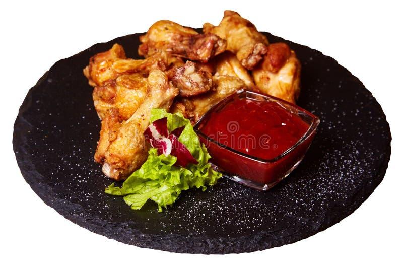 Palillos asados a la parrilla de las piernas de pollo en un tablero negro fotos de archivo