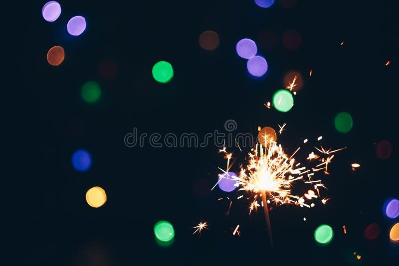 Palillos chispeantes de las bengalas de Bengala en llamas en un fondo negro con el bokeh de las luces fondo del Año Nuevo del tem fotos de archivo