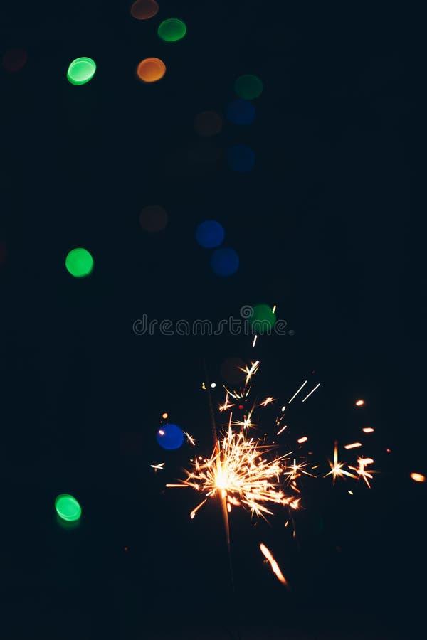 Palillos chispeantes de las bengalas de Bengala en llamas en un fondo negro con el bokeh de las luces fondo del Año Nuevo del tem fotografía de archivo