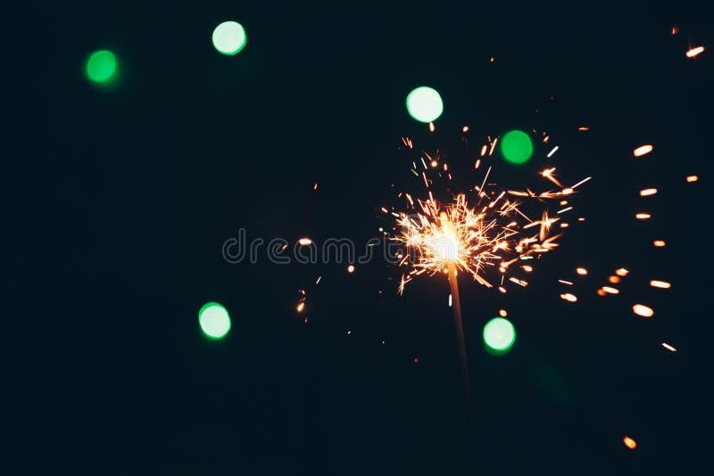 Palillos chispeantes de las bengalas de Bengala en llamas en un fondo negro con el bokeh de las luces fondo del Año Nuevo del tem foto de archivo libre de regalías