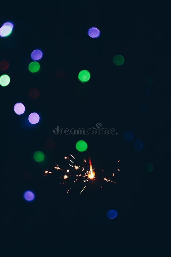 Palillos chispeantes de las bengalas de Bengala en llamas en un fondo negro con el bokeh de las luces fondo del Año Nuevo del tem imagenes de archivo